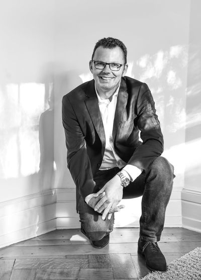 Full length portrait of businessman kneeling against wall at home