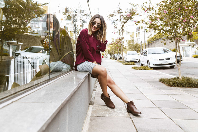 Portrait Of Smiling Young Woman Sitting On Sidewalk By Glass Building
