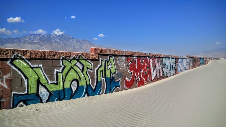Colorful graffiti wall by sandy beach against sky