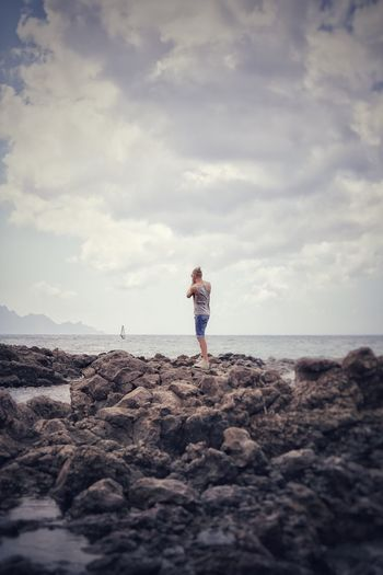 Rear view of young man standing on rock at beach against cloudy sky