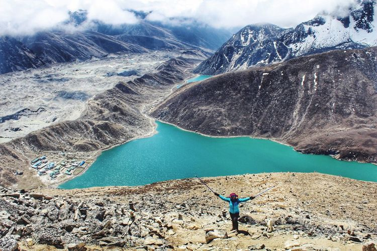 High angle view of woman standing by lake against mountain