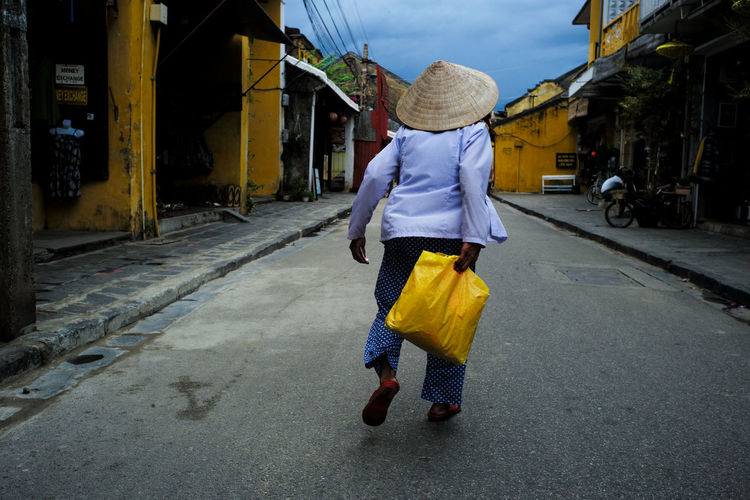 The hunt for conical hats #2 Walking Away Vietnam Hat Vietnamese Women Breeze Conical Hat Hoi An Leading Lines Old Town Showcase September Street Streetphotography Vietnam Leica Summicron