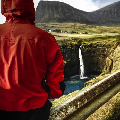 Rear view of man standing at riverbank