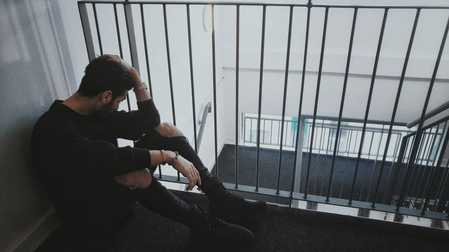 Full length of depressed man sitting by railing in building