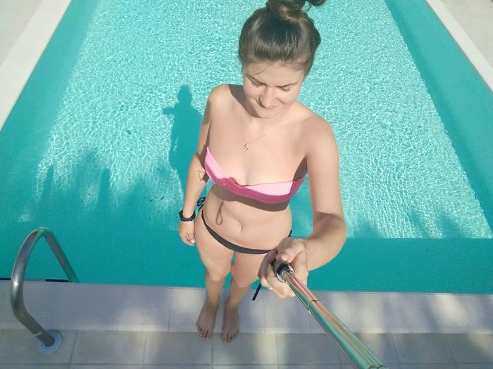 Sensuous Young Woman Wearing Bikini Taking Selfie From Monopod At Poolside On Sunny Day