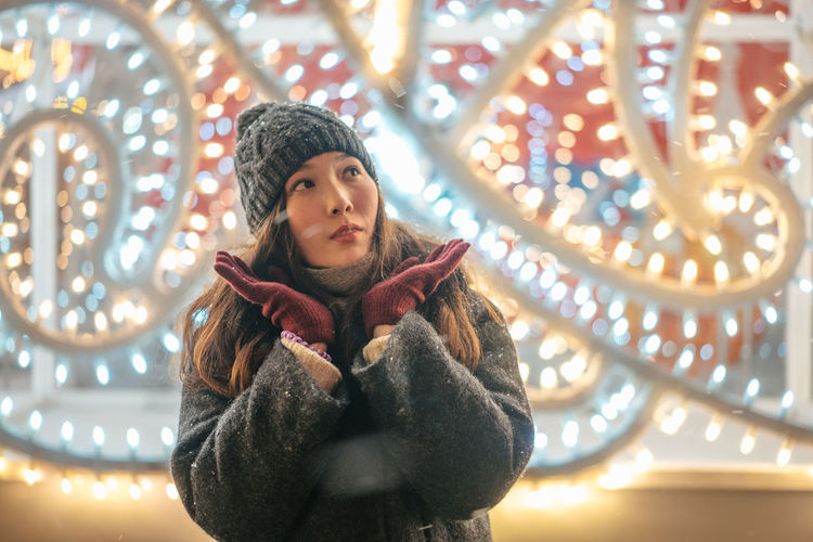 Christmas Christmas Decoration Portrait New Year Illuminated Warm Clothing Leisure Activity Lifestyles Front View Lighting Equipment One Person Young Adult Clothing Women Looking Real People Winter Casual Clothing Young Women Waist Up Glowing Scarf Outdoors Contemplation