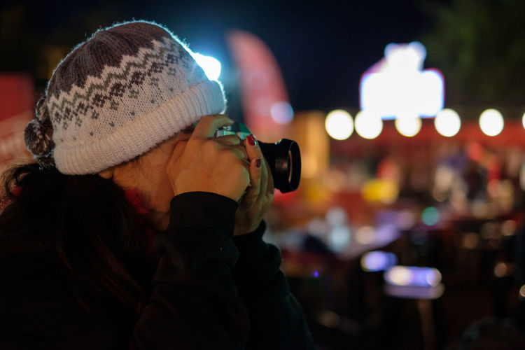 Midsection of woman photographing illuminated city at night