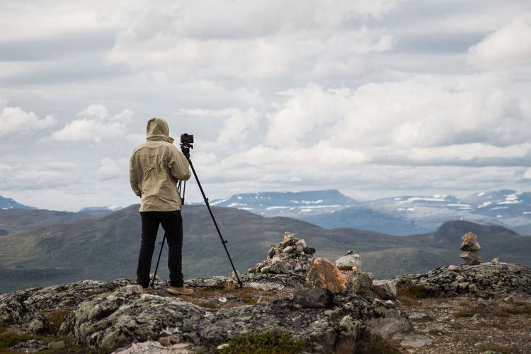 Rear view of man photographing on cliff against cloudy sky