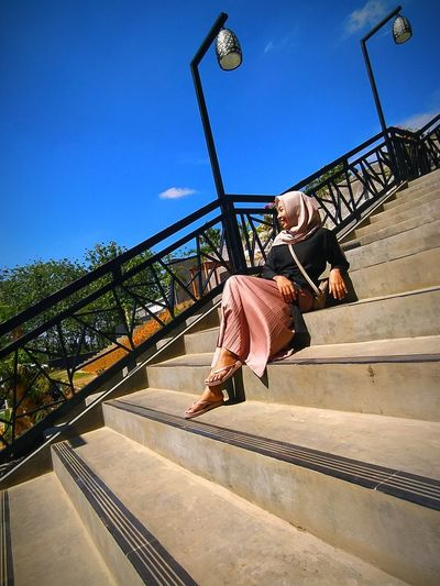 Low angle view of woman sitting on steps against clear sky