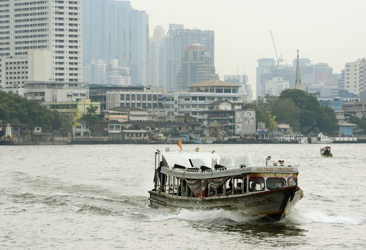 Ferry Boat In River Against Buildings In City