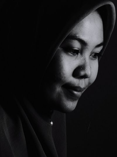 Close-up of young woman against black background