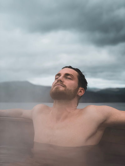 Portrait of young man in water against sky