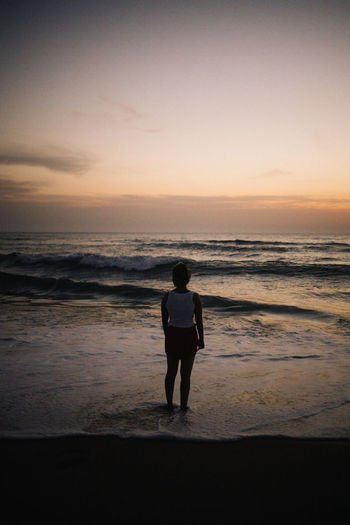 Rear view of woman standing on beach watching sunset