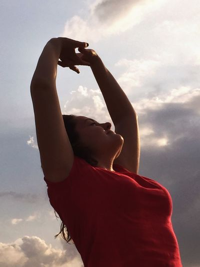 Low angle view of happy woman standing with arms raised against sky