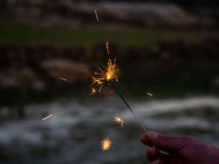 Hand holding sparkler at night