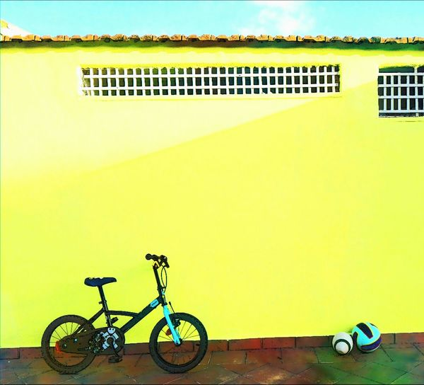 Bicycle against yellow wall of building