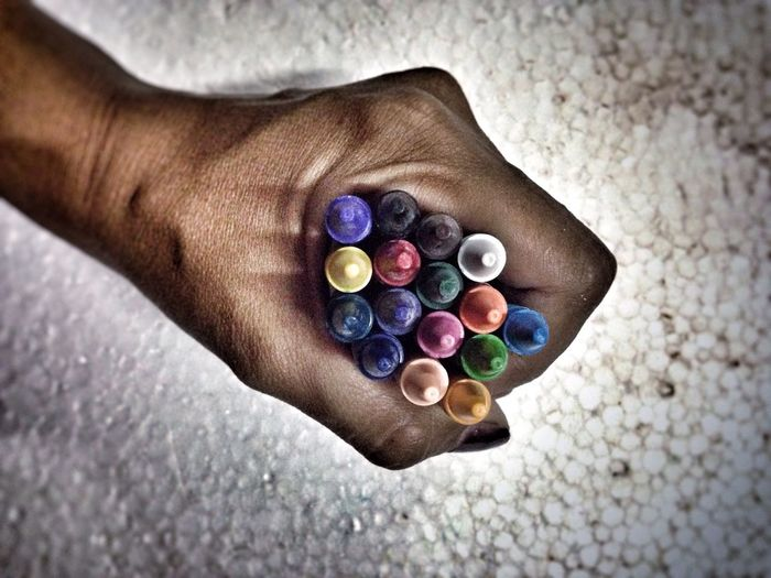 Cropped hand holding colorful crayons