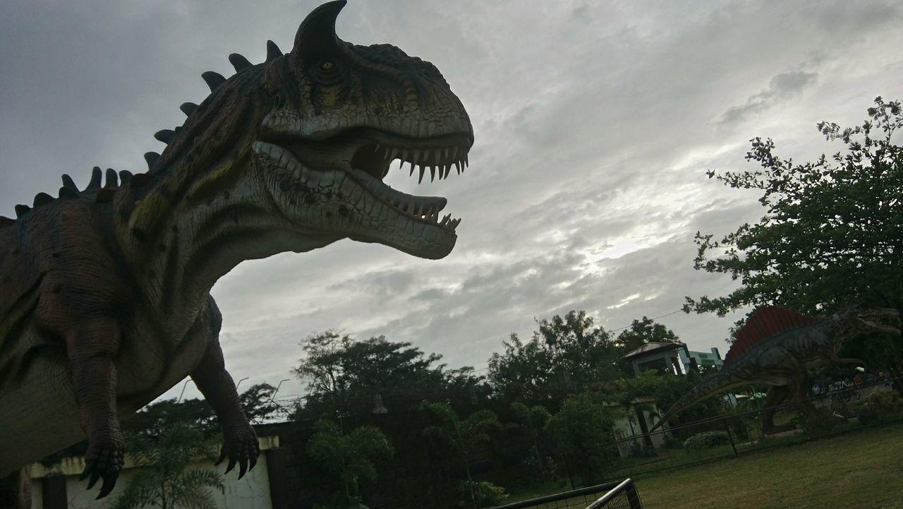 statue, sculpture, animal representation, sky, cloud - sky, dinosaur, low angle view, outdoors, day, no people, gargoyle, tree, nature