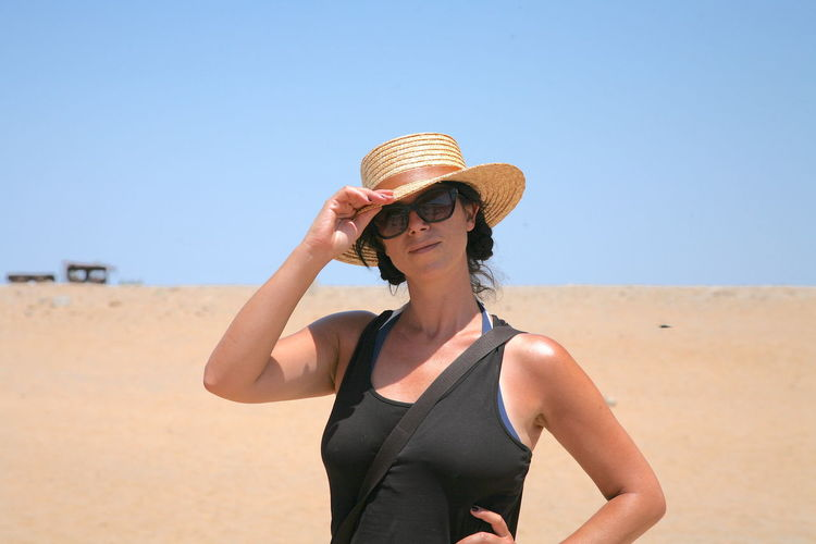 Young woman wearing sunglasses standing on beach against clear sky