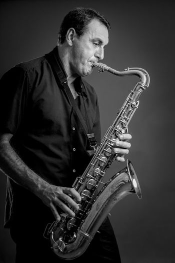 Portrait of adult playing saxophone. Adult Adults Only Jazz Music Mature Men Men Music Musical Instrument Musician One Man Only One Person Only Men People Performance Playing Portrait Real People Saxophone Studio Shot