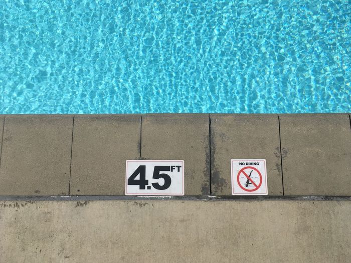 No diving sign and number on poolside