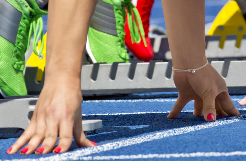 Low section of people at starting block on running track