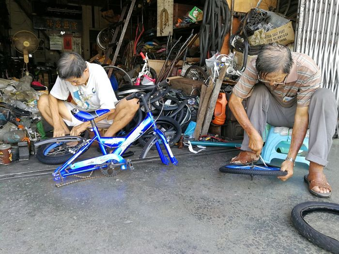 98 years bicycle shop. Sitting Day Adults Only Full Length Adult Only Women Outdoors One Person Lifestyles One Woman Only Real PeoplePeople