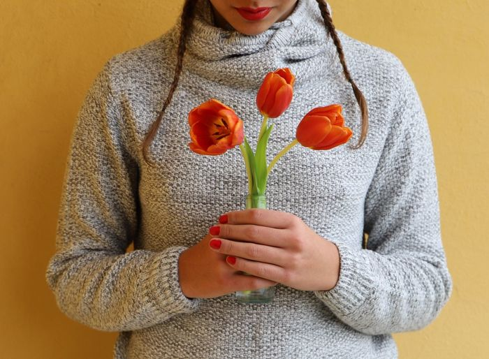 Midsection Of Woman Holding Flowers Against Orange Background