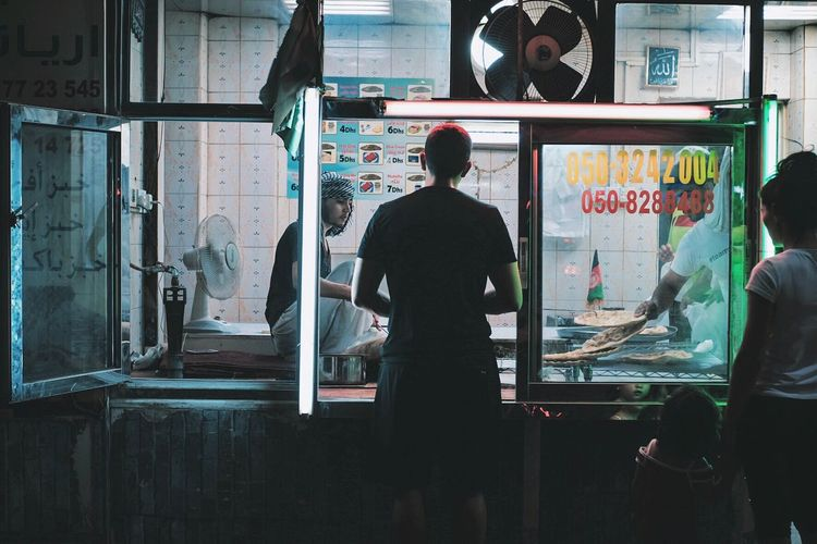 Rear view of people standing in glass window