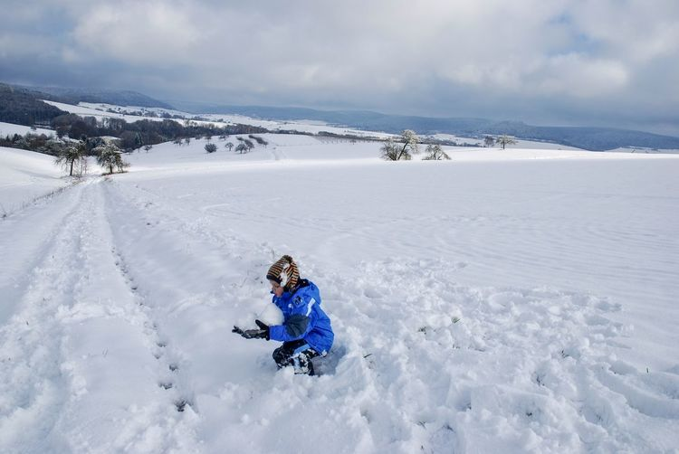 A boy  skiing on snowcapped field against sky