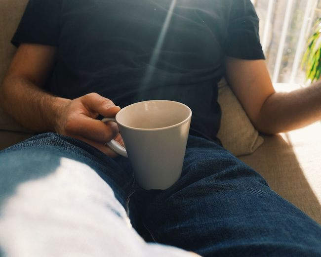 Midsection Of Man Having Coffee While Sitting On Sofa At Home