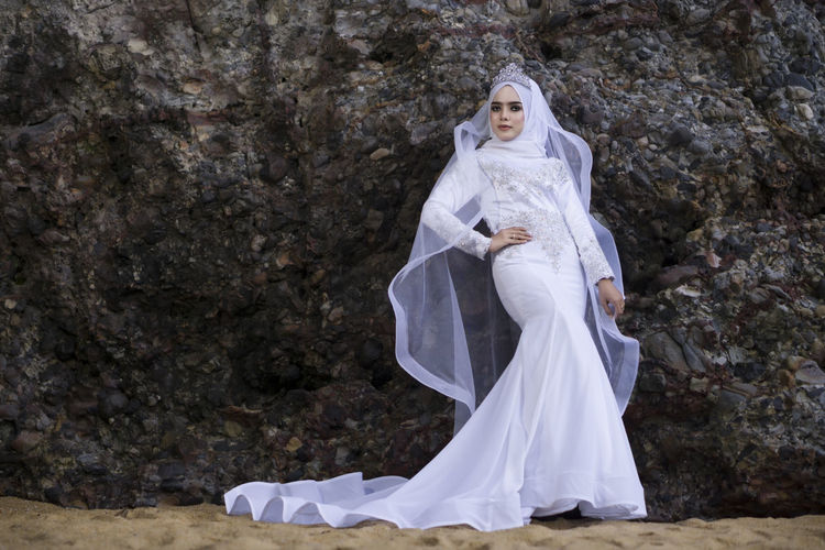 Portrait of beautiful bride standing against rock formation at beach