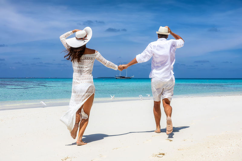 Happy traveler couple running down a tropical beach and having fun on their honeymoon Sea Beach Water Two People Land Real People Full Length Sky Hat Horizon Horizon Over Water Togetherness Women Scenics - Nature Leisure Activity Rear View Lifestyles Couple - Relationship Positive Emotion Summer Clothes Fashion Honeymoon Love Happiness Happy Tropical Climate Maldives Running Fun Tropics Travel Island Turquoise Water Ocean