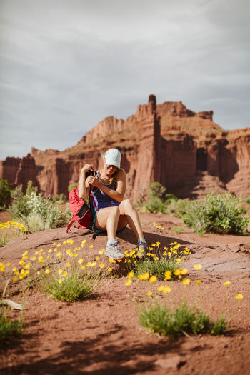 Woman sitting on rock formation against sky