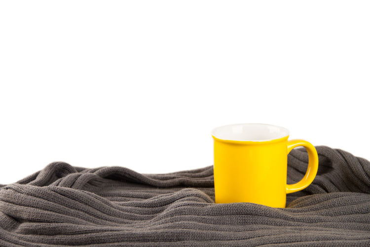 Close-up Clothing Coffee Cup Copy Space Cup Drink Focus On Foreground Food And Drink Freshness Indoors  Mug No People Refreshment Scarf Still Life Studio Shot Sweater Textile Warm Clothing White Background Wool Yellow