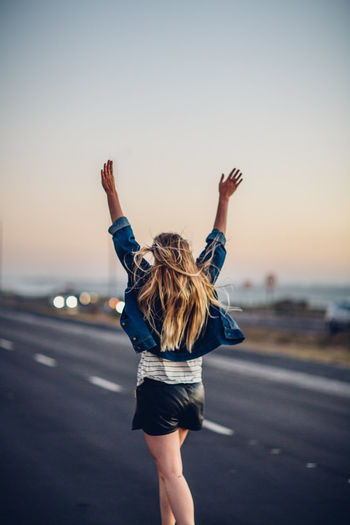 Rear view of young woman with arms raised walking on road against clear sky during sunset