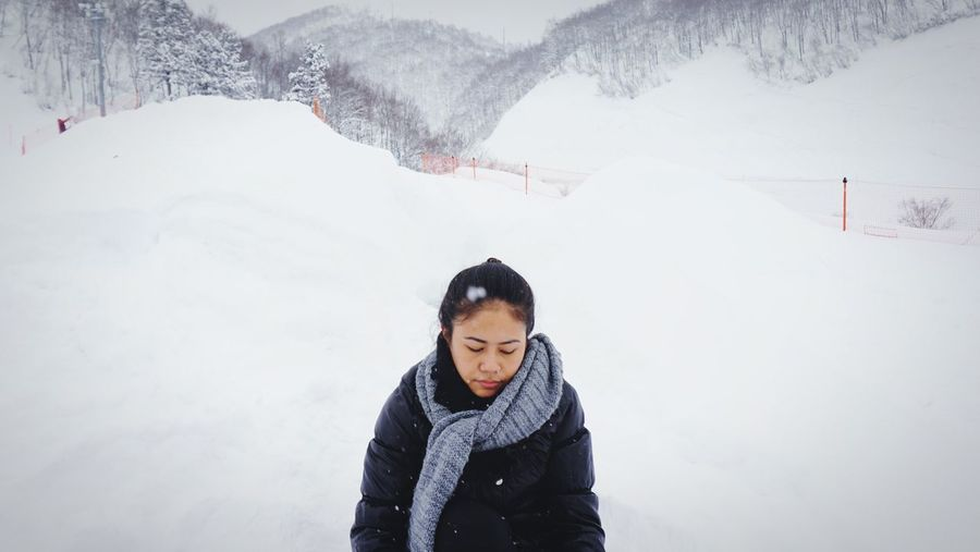 Young woman standing on snowcapped mountain