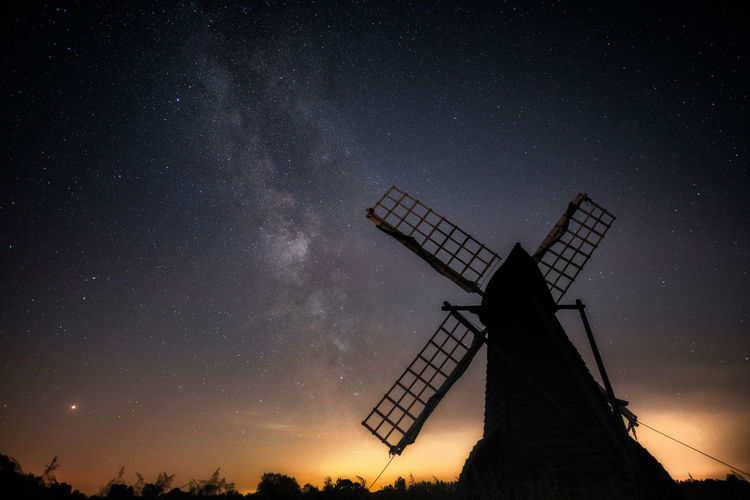 Low angle view of silhouette traditional windmill against sky at night
