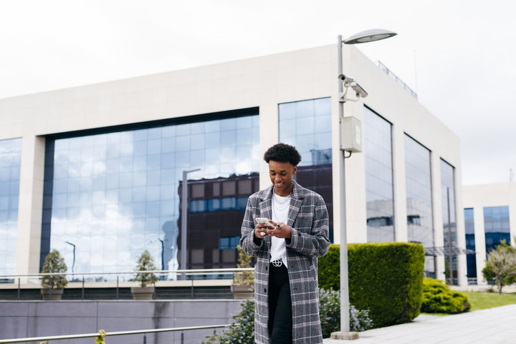 Young man using mobile phone against sky