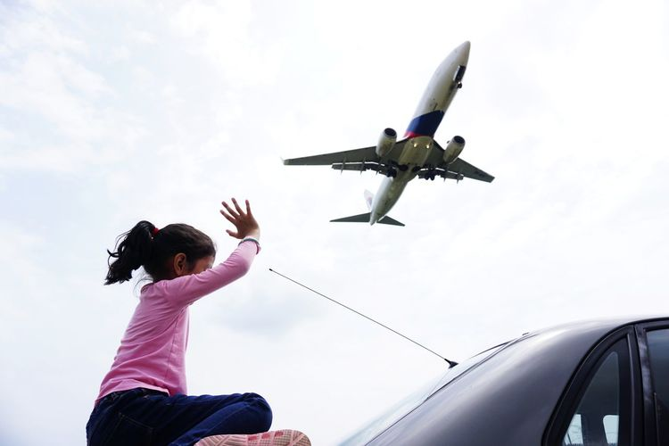Low angle view of woman flying airplane against sky