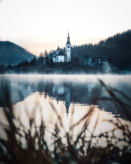 Bled Water Built Structure Architecture Building Exterior Sky Nature Reflection Place Of Worship Clear Sky Plant No People Building River Religion Belief Outdoors Tree Spire  Mountain