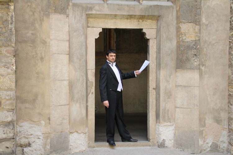 Portrait Of Businessman Holding Document While Standing At Doorway