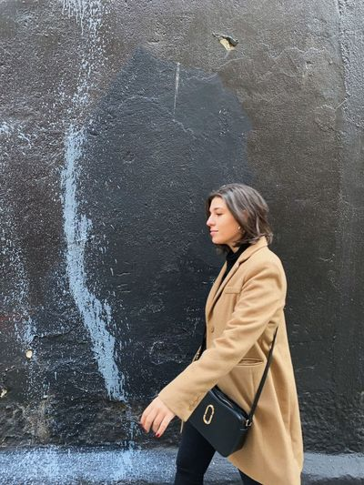 Side view of young woman walking against wall
