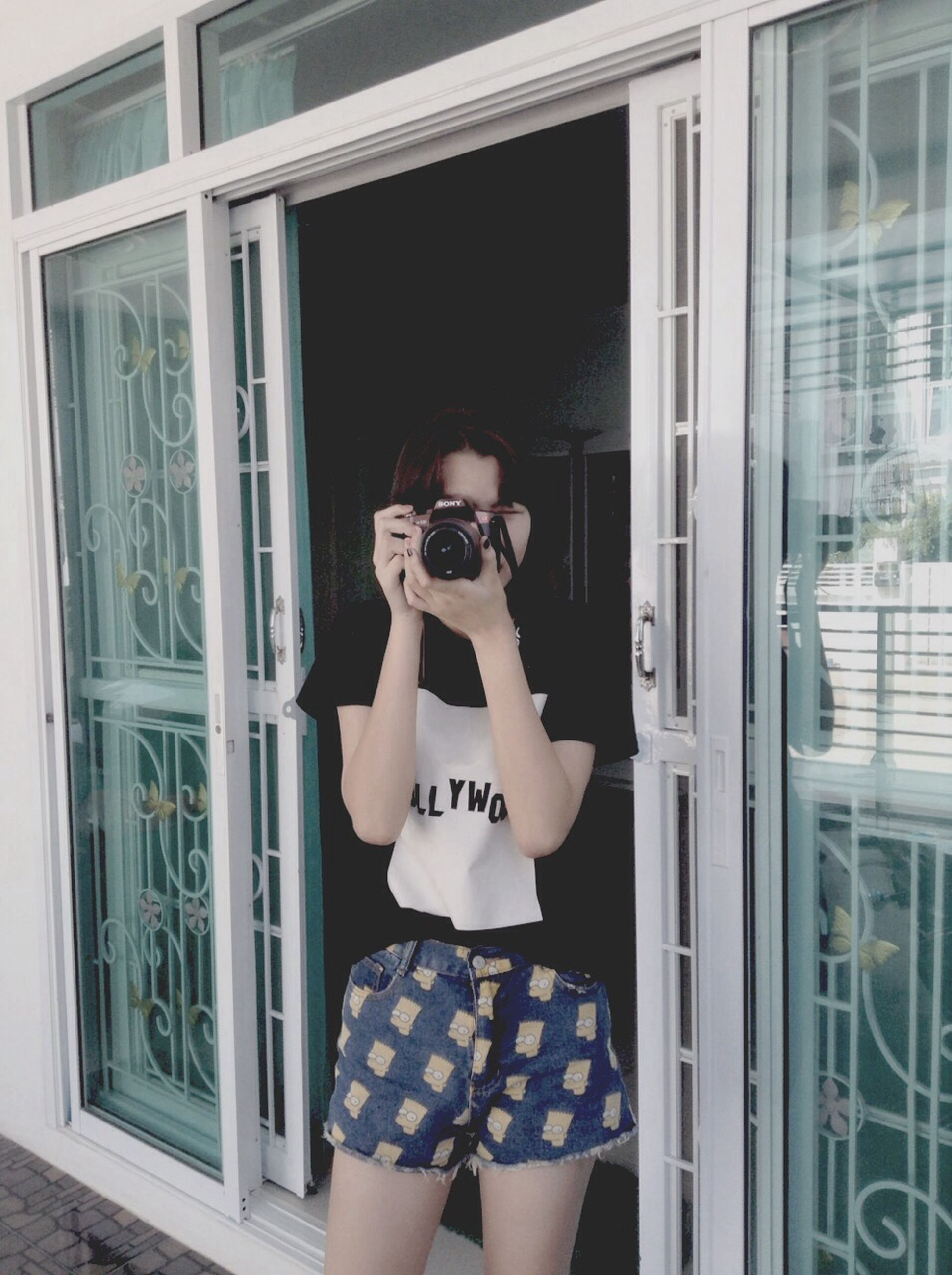 lifestyles, young adult, leisure activity, architecture, built structure, front view, holding, building exterior, young women, person, standing, photography themes, window, looking at camera, sunglasses, photographing, reflection, casual clothing