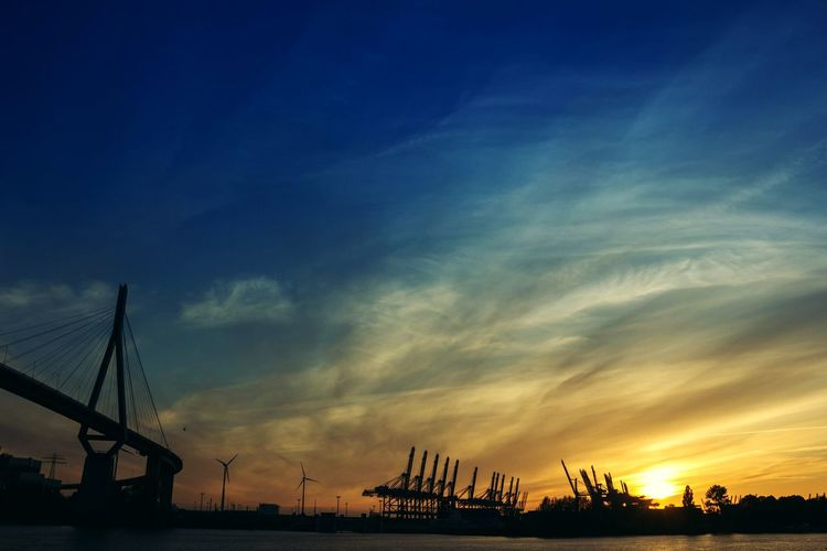 Silhouette cranes at dock against sky during sunset