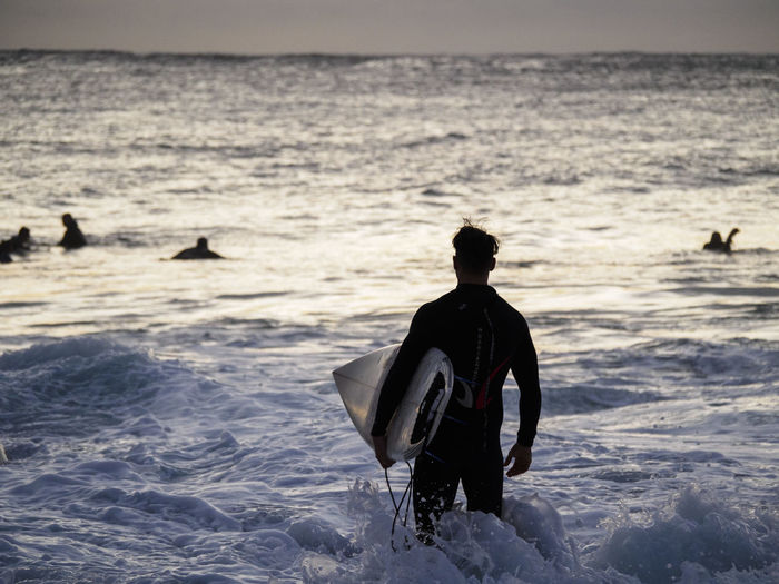 Man with surfboard standing in sea against sky