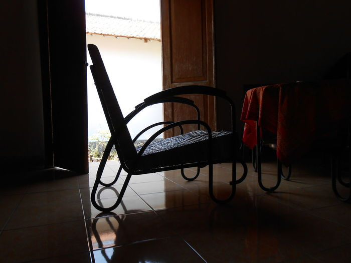 Empty chair and table in dark room by door