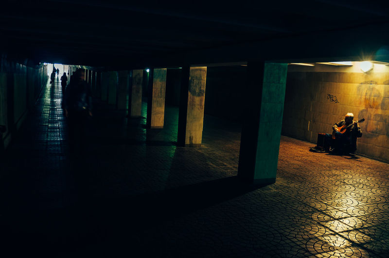 Illuminated Built Structure Indoors  Real People Subway Men Architectural Column Public Transportation People Transportation Walking Lifestyles Women Full Length Travel Rear View Direction Underpass Flooring Light Ceiling Guitar Guitarist Music Musician
