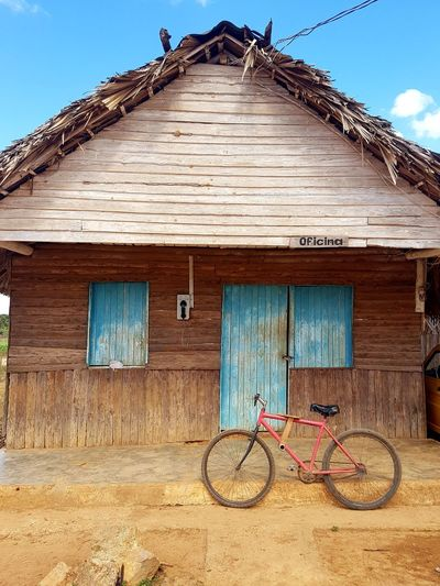 Bicycle parked by barn against sky