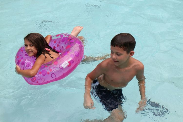 Brother and sister enjoying in swimming pool
